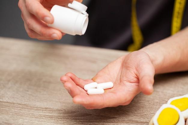 男は彼の手で毎日の食事療法に錠剤バイオ添加物を保持しています