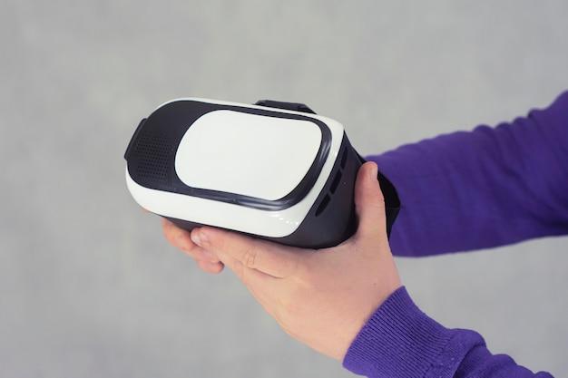 男は、バーチャルリアリティと360度ビデオ用の眼鏡を手に持っています。明るい背景のスマートフォン用vrヘルメット。