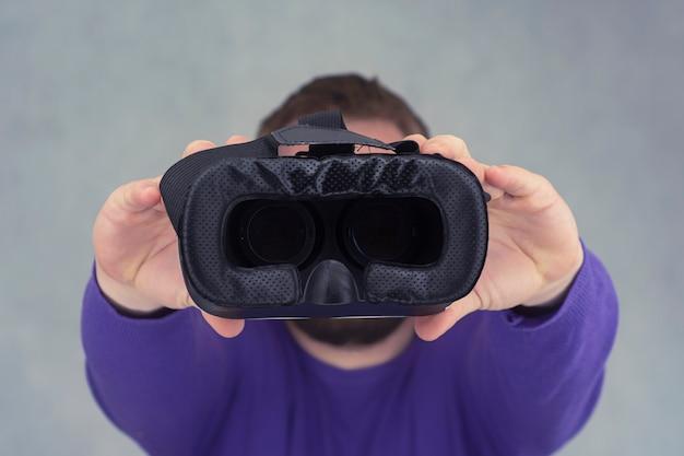Мужчина держит в руках очки для виртуальной реальности и 360-градусного видео. vr-шлем для смартфона на светлом фоне.