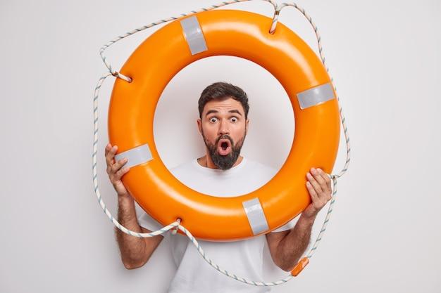 Мужчина держит надутый спасательный круг смотрит с упущенными глазами с широко открытым ртом учится плавать, готовый спасти вас, одетый в повседневную футболку на белом