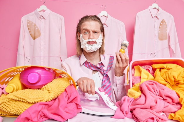 Man holds iron and shaving brush busy ironing laundry clothes works hard during weekends poses on clotheslines on pink
