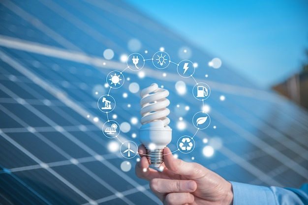 The man holds a light bulb, led bulb on a background of solar panels with icons energy sources for renewable