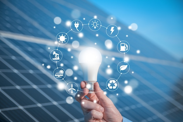 The man holds a light bulb, led bulb on solar panels with icons energy sources for renewable, sustainable development. ecology concept.