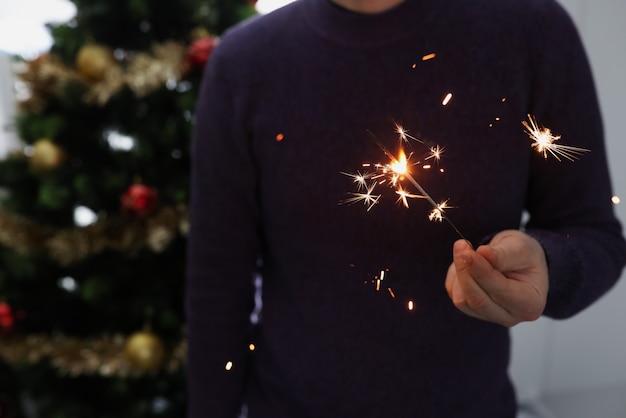 Мужчина держит зажженный бенгальский огонь в темной концепции празднования нового года и рождества