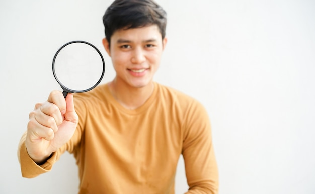 Man holds magnifier glass for searching