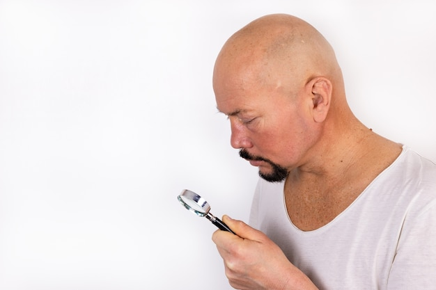 A man holds a magnifying glass in his hands