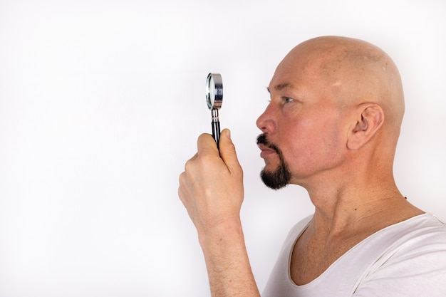 A man holds a magnifying glass in his hands.