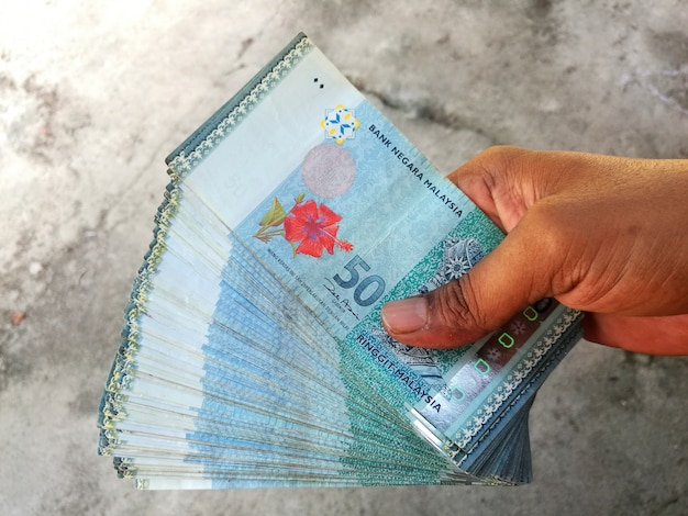 Man holds malaysian ringgit banknotes on gray textured background