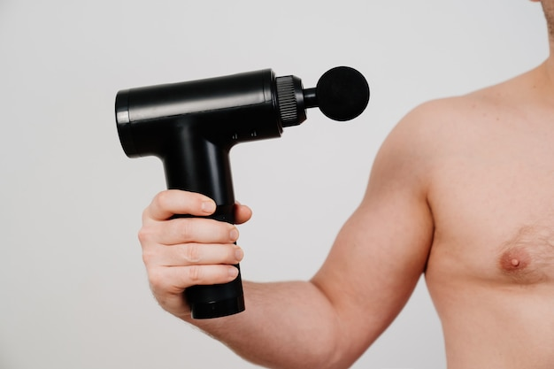 남자는 마사지 총을 보유하고 있습니다. 의료 스포츠 장치는 훈련 후 근육통을 줄이고 피로를 완화하며 신체의 문제 부위에 영향을 미치고 피부 상태를 개선하는 데 도움이 됩니다.