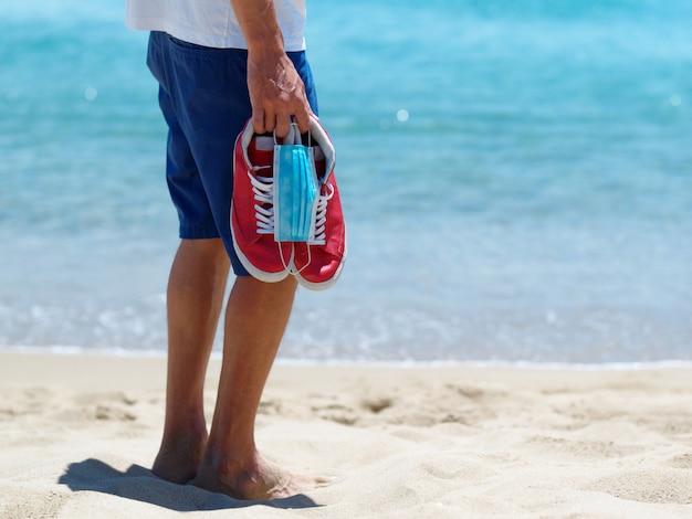 男はサンディトロピカルビーチで医療マスク、赤いスニーカーを保持しています。コンセプト夏休み2020。