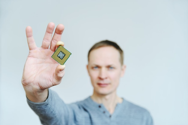 Man holds a microchip in his fingers.