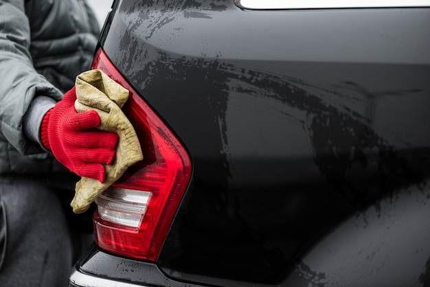 The man holds the microfiber in hand and polishes the back headlights car closeup.