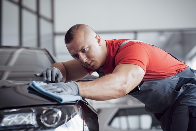 The man holds the microfiber in hand and polishes the car. the new machine is being prepared for sale