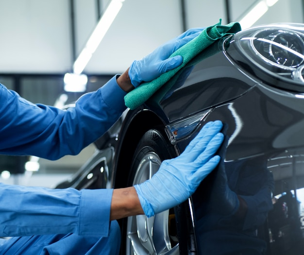Man holds the microfiber in hand and polishes the car