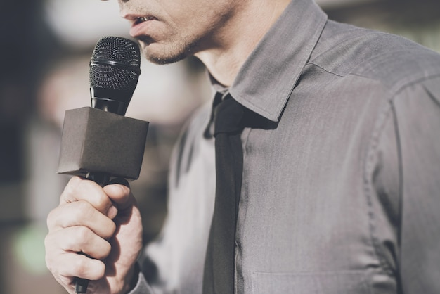 A man holds a microphone and speaks into it.