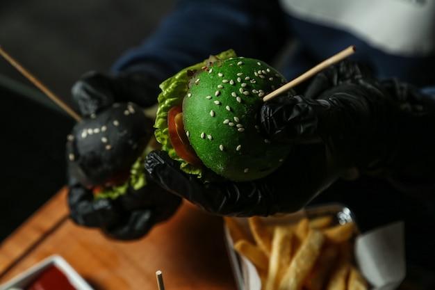 L'uomo tiene gli hamburger misti sulla vista superiore della cipolla del cetriolo del pomodoro della lattuga della carne del bordo di legno