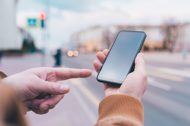 A man holds a mock-up of a smartphone on the background of the road.