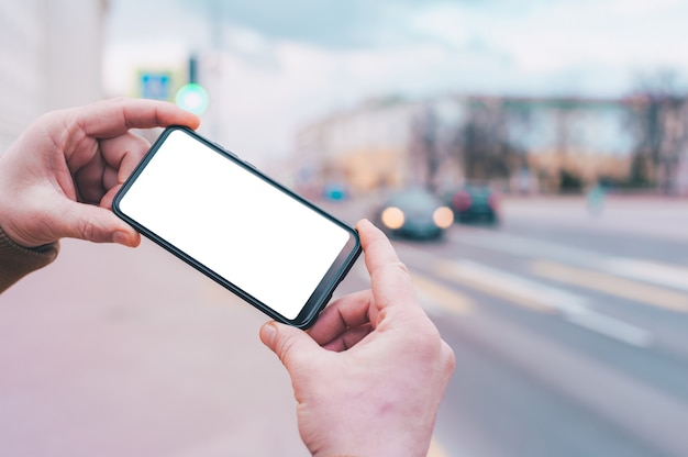 A man holds a mock-up of a smartphone with a white screen on the background of the road.