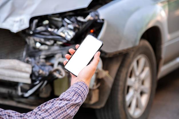 男は自動車事故の後にモックアップ携帯電話の白い電話の画面を手に持っています。交通事故の場所にウェブアプリで保険サービスを呼び出します。難破した車の前のスマートフォン。