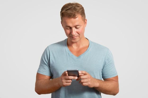 L'uomo detiene il moderno smartphone, messaggi di testo, controlla la sua casella di posta elettronica, collegato a internet wireless