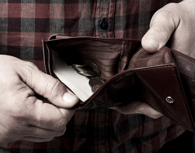 Man holds an open brown leather wallet with ukrainian hryvnia coins, poverty concept