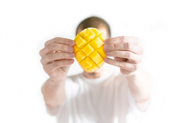 Man holds an open mango in front of him face.