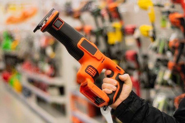 Man holds an orange reciprocating saw for repair work against the backdrop of showcases in a hardware store.