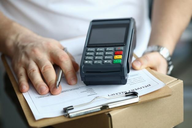 Мужчина держит посылку с документом и терминалом