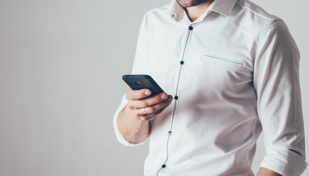 A man holds a phone in his hand. he is dressed in a white shirt