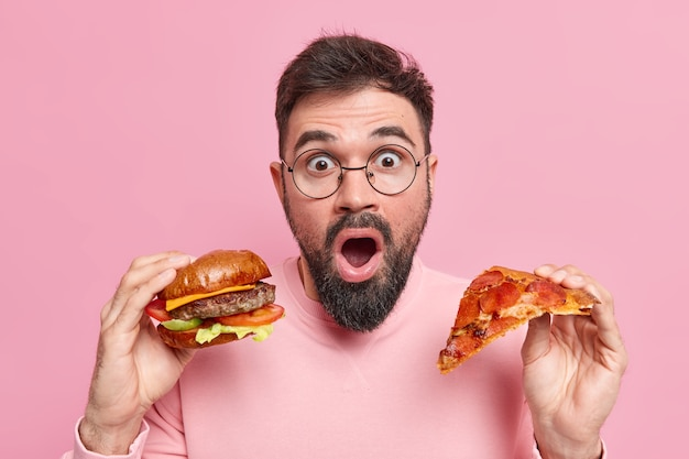 Man holds piece of pizza and hamburger eats junk food shocked to consume much calories wears round spectacles casual jumper