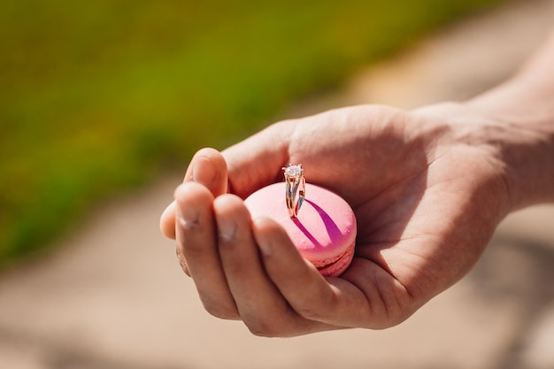 Man holds pink macaroon with wedding ring