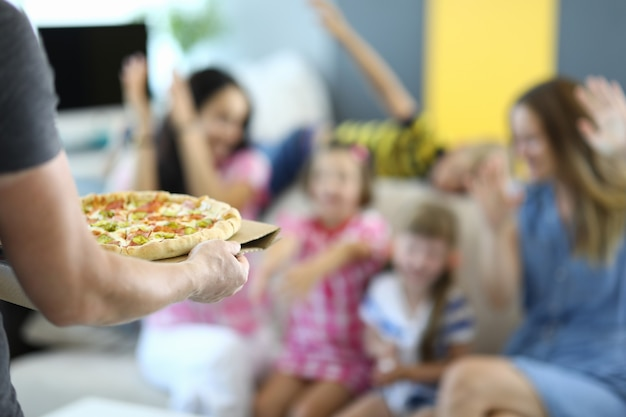Man holds pizza in his hands, rejoicing children and adults.