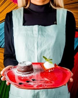 L'uomo tiene il piatto con cioccolato fondente vista laterale