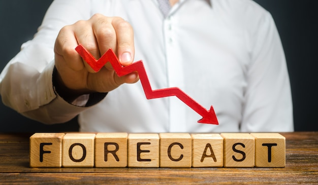 Man holds red arrow down over word forecast. a budget shortage, recession economy