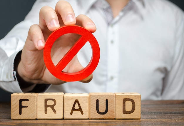 A man holds a red no prohibition symbol over word fraud countering deception