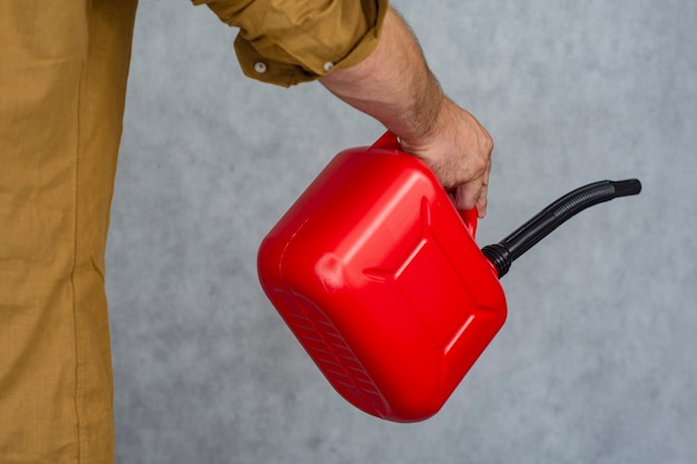 Man holds a red plastic gas canister in his hands.