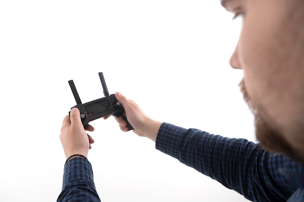 Man holds the remote control from the quadcopter on a white