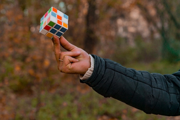 Man holds rubik's cube outdoor in the park. hand. arm. logical game. combination puzzle. training brain