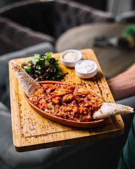 Мужчина держит морепродукты фахитас креветки овощи сыр лаваш зеленый салат сметана вид сбоку