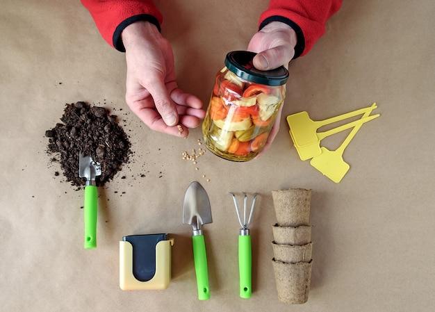 男は自分の庭から植えるための種と既製の缶詰野菜を持っています。