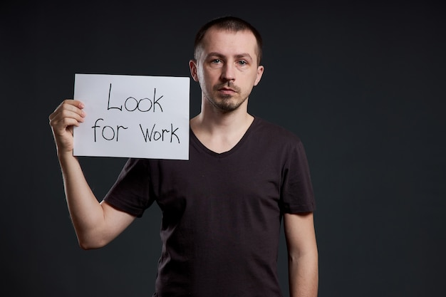 Man holds a sign with the words looking for work, unemployment and crisis