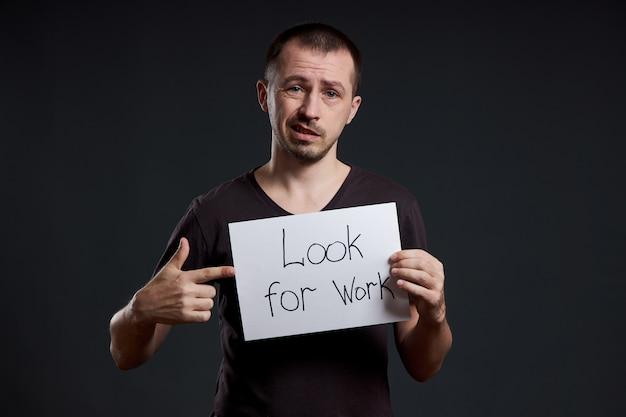 Man holds a sign with the words looking for work