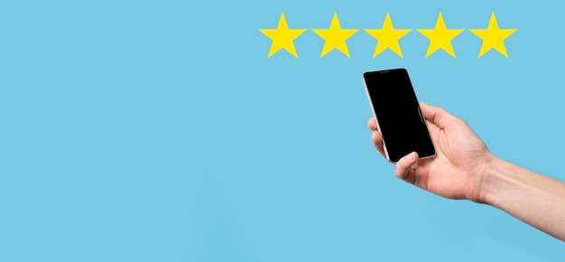 Man holds smart phone in hands and gives positive rating, icon five star symbol to increase rating of company concept on blue background. customer service experience and business satisfaction survey.