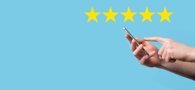 Man holds smart phone in hands and gives positive rating, icon five star symbol to increase rating of company concept on blue background.