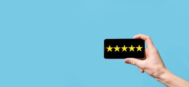 男はスマートフォンを手に持って、青い背景に会社のコンセプトの評価を上げるために肯定的な評価、アイコン5つ星のシンボルを与えます。カスタマーサービスの経験とビジネス満足度調査。