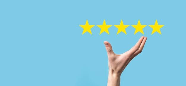 남자는 손에 스마트 폰을 들고 긍정적 인 평가, 파란색 배경에 회사 개념의 등급을 높이기 위해 아이콘 5 성급 기호를 제공합니다. 고객 서비스 경험 및 비즈니스 만족도 조사.