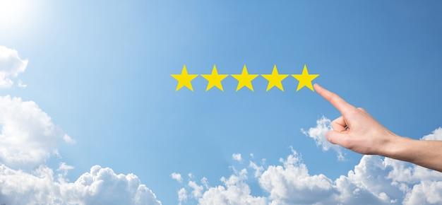 Мужчина держит смартфон в руках и дает положительный рейтинг, значок пяти звездочек для повышения рейтинга концепции компании на синем фоне. опыт обслуживания клиентов и опрос удовлетворенности бизнесом.