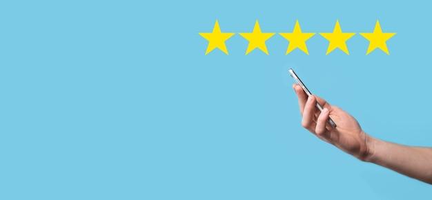 Мужчина держит смартфон в руках и дает положительный рейтинг, значок пятизвездочный символ для повышения рейтинга концепции компании на синей поверхности