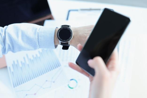 男はスマートフォンを手に持ってスマートウォッチを見ています。健康監視のためのスマートウォッチ