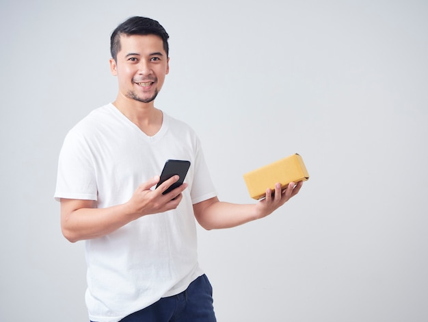 Man holds smartphone and parcel box